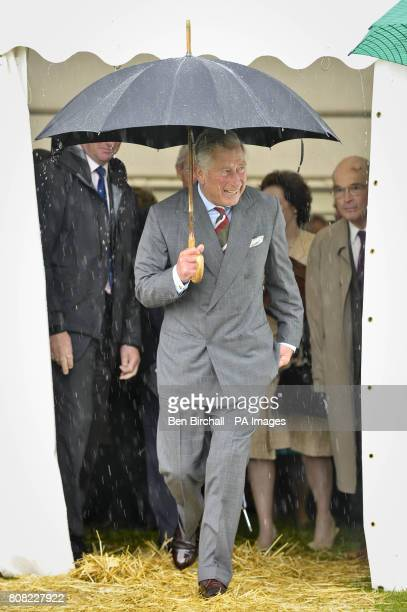The Prince of Wales laughs as he emerges from a craft tent into a heavy downpour at the National Botanic Gardens of Wales in Carmarthen as he...