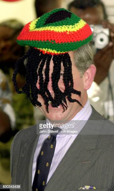 The Prince of Wales laughs with the local Rasta community as he wears a Rasta hat at the Trenchtown community centre in Kingston Jamaica during his...