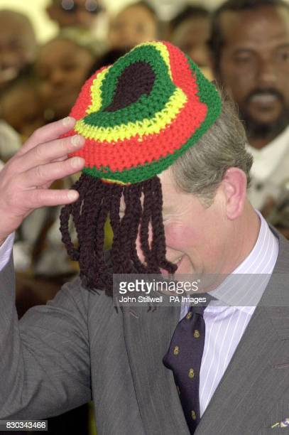 The Prince of Wales laughs with the local Rasta community as he wears a Rasta hat during his visit to the Trenchtown community centre in Kingston...