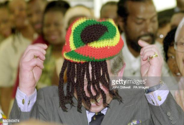 The Prince of Wales laughs with the local Rasta community as he wears a Rasta hat during a visit to the Trenchtown community centre in Kingston...