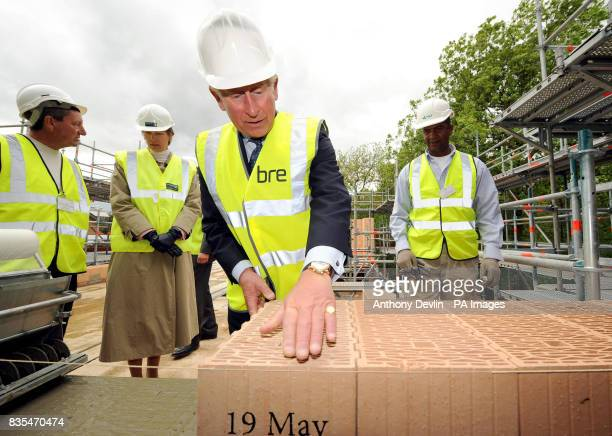 The Prince of Wales lays a thermoplan block with site manger Wilf Jordan as he visits the Building Research Establishment Innovation Park to view...