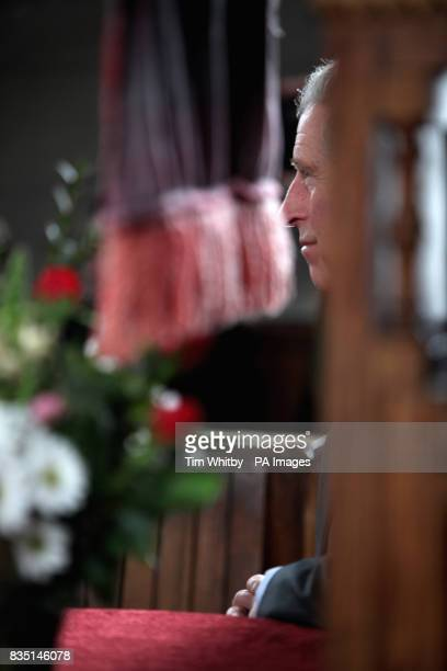 The Prince of Wales listens to the 'Fron' male voice choir perform during his visit to Froncysyllte winner of the Calor Gas Village of the Year near...