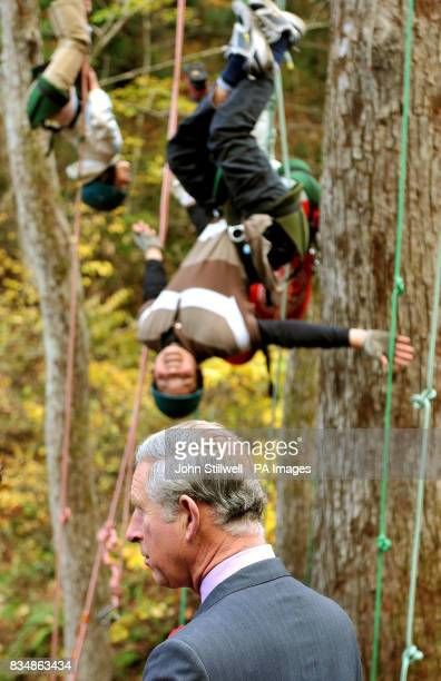 The Prince of Wales looks on as children hang upside down from trees during a visit to the Afan Forest near the village of Shinanomachi in central...