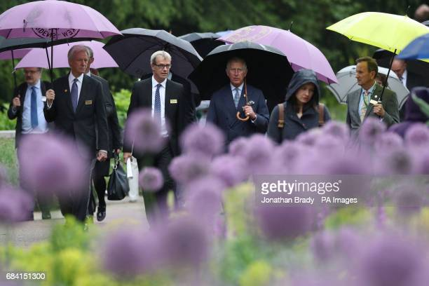 The Prince of Wales passes allium flowers planted in the Great Broad Walk Borders at the Royal Botanic Gardens at Kew Richmond Surrey