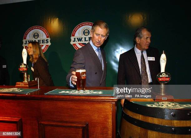 The Prince of Wales picks up a pint of beer from behind the bar during a visit to the JW Lees Brewery at Middleton near Manchester Members of the...