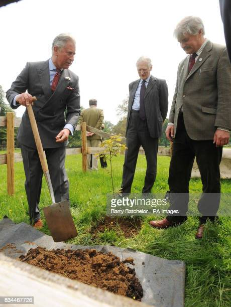 The Prince of Wales plants a tree watched by Lord Lieut of Gloucestershire Henry Elwes and the Highgrove Head Gardener David Howard in the grounds of...