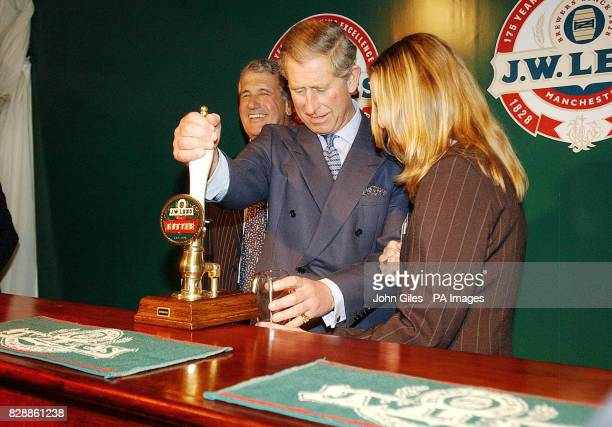 The Prince of Wales pulls himself a pint of beer from the pump during a visit to the JW Lees Brewery at Middleton near Manchester Members of the...