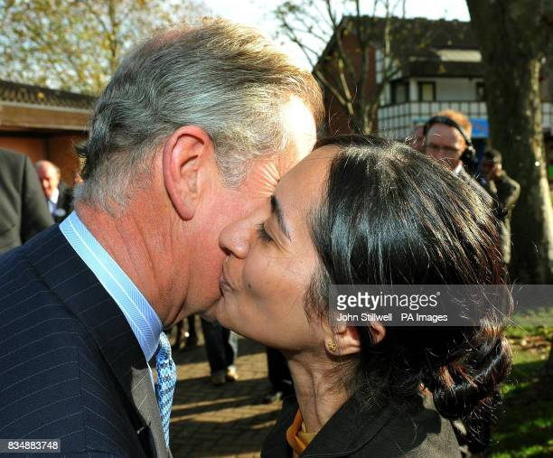 The Prince of Wales receives a kiss from a woman as he leaves a Prince's Trust project at Beckton Community Centre in east London