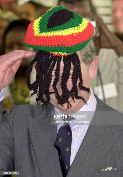 The Prince of Wales salutes the local Rasta community as he wears a Rasta hat during a visit to the Trenchtown community centre in Kingston Jamaica...