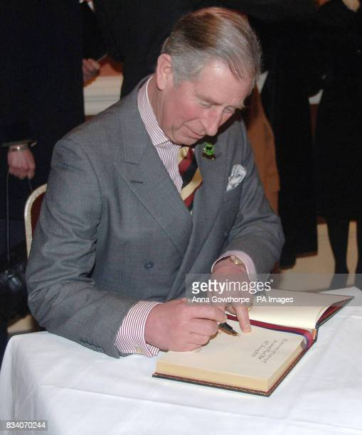 The Prince of Wales signs a book during his visit to officially reopen the Royal Hall in Harrogate after its restoration