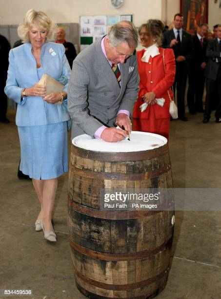 The Prince of Wales signs a whiskey barrel at the Bushmills whiskey distillery in Co Antrim as the Duchess of Cornwall looks on