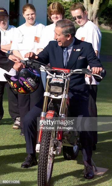 The Prince of Wales straddles a trials bike during a visit to Prince's Trust beneficiaries at Government House Onchana as part of a twoday trip to...