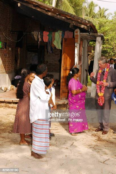The Prince of Wales talks to a family outside their partially destroyed home in Maddikkali on the Eastern coast of Sri Lanka where the recent Tsunami...