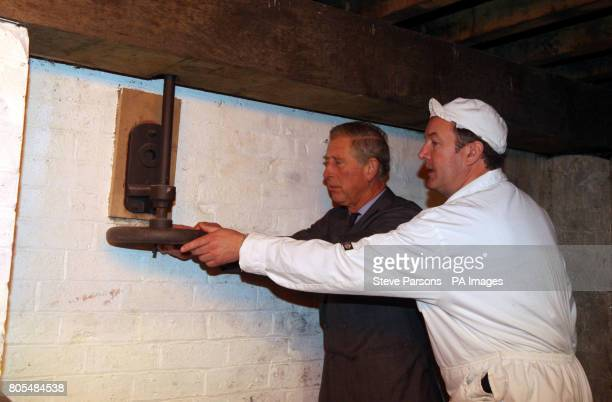 The Prince of Wales turns a wheel with Matt Bowman to start the Stanway Watermill in the village of Stanway in Glouchestershire