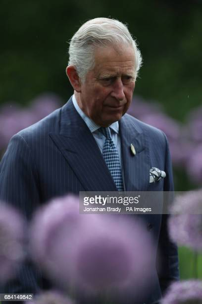 The Prince of Wales views allium flowers planted in the Great Broad Walk Borders at the Royal Botanic Gardens at Kew Richmond Surrey