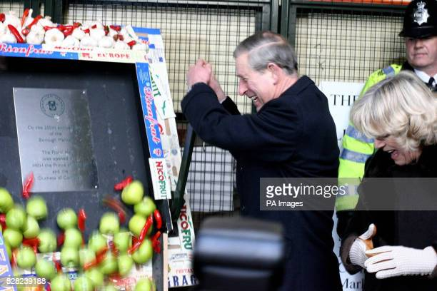 The Prince of Wales watched by the Duchess of Cornwall pulls a lever to send apples tumbling into a bucket revealing a plaque during a visit to the...