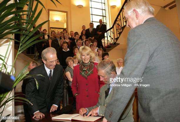 The Prince of Wales watched by the Duchess of Cornwell signs the visitor book as they open Walkers Shortbread Head office at Aberlour House in the...