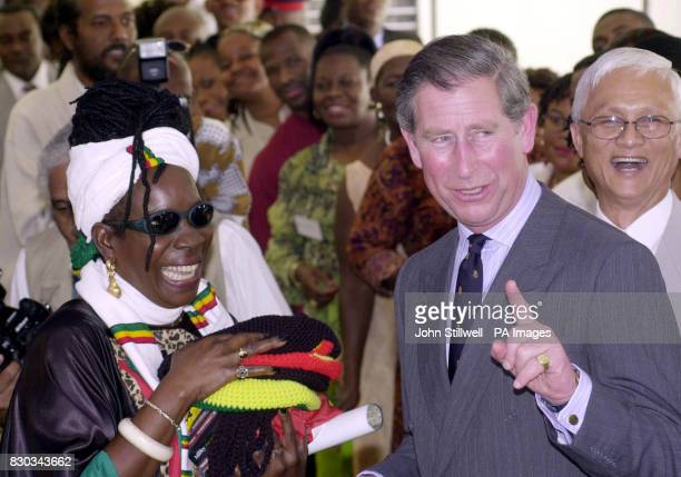 The Prince of Wales with reggae legend Bob Marley's widow Rita asks the media to wait one second as he prepares to wear a Rasta hat at the Trenchtown...