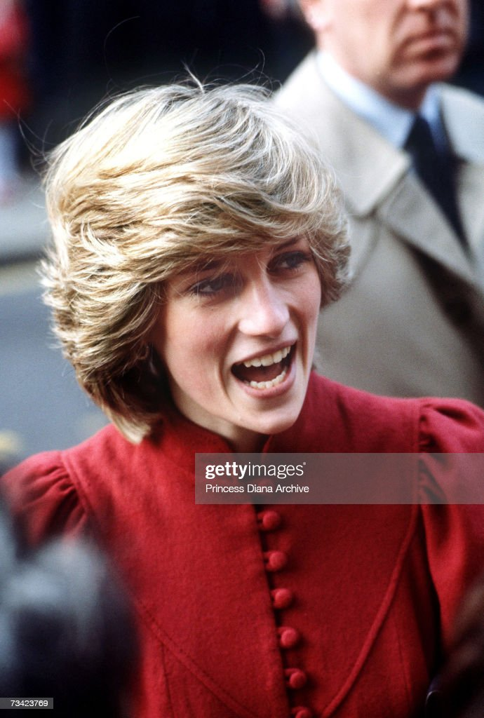 The Princess of Wales visits the DHSS in Wandsworth, London, 6th December 1982. She is wearing a red suit by Caroline Charles.