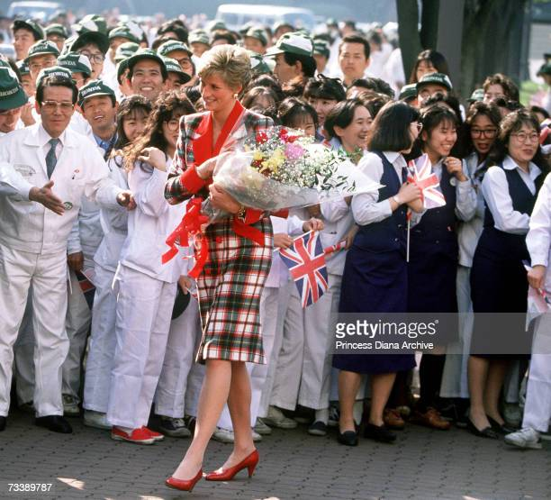 The Princess of Wales with workers at the Honda factory in Tokyo during a visit to Japan November 1990 She is wearing a Catherine Walker tartan...