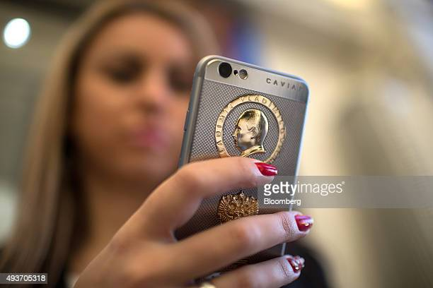 The profile of Vladimir Putin Russia's president sits above the coat of arms of the Russian Federation on the rear casing of an 18 carat gold plated...