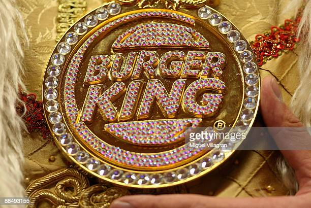 The promotional figure 'The King' wears fake jewelry depicting the Burger King logo during the opening of the first European Whopper Bar on June 15...