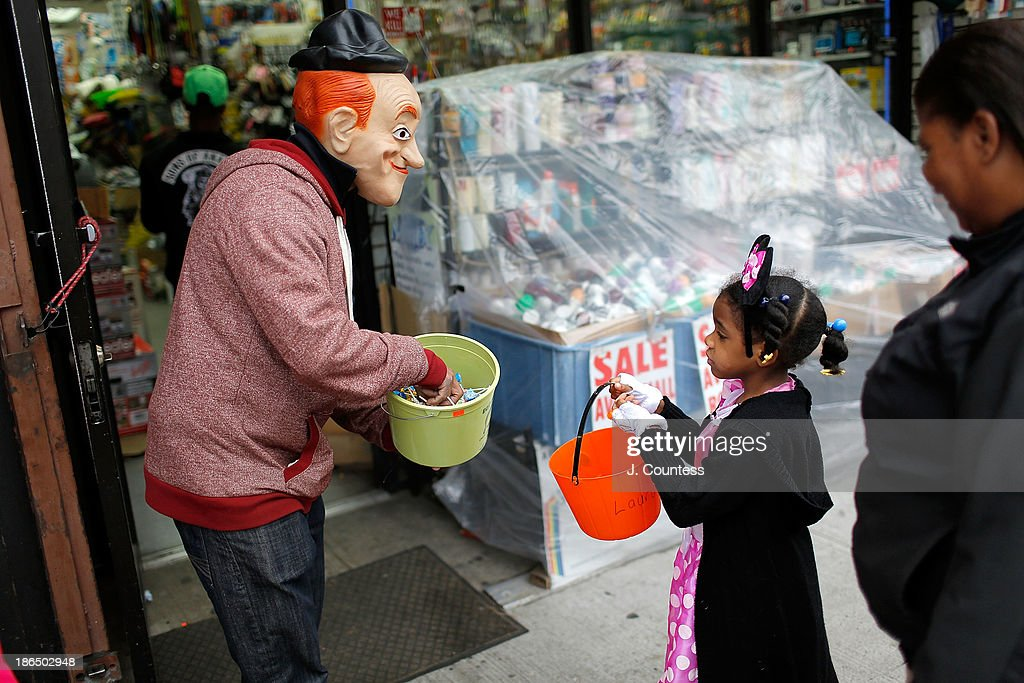 The proprietor of the Big Brothers Discount Hardware Store on Fulton Avenue serves candy to 'trick or treaters' in the heart of 'Bedstuy' as they 'Trick or Treat' at local businesses on Fulton Ave. on October 31, 2013 in New York City.