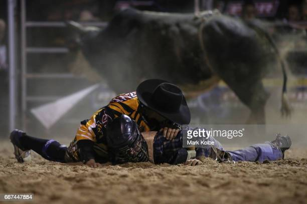 The protection athletes lies over the motionless Jay Borghero of Rockhampton to protect him after he was injured by the bull Hotter Than Hell 2 after...