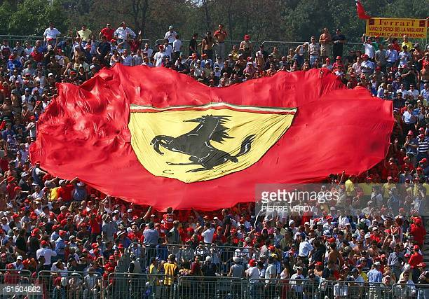the public hold a big Ferrari flag before the start of the Italian Formula One Grand Prix 10 September 2000 on the Monza racetrack AFP PHOTO PIERRE...