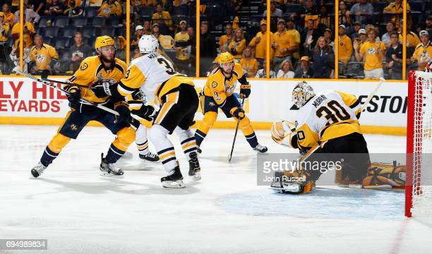 The puck almost squeezes past Matt Murray of the Pittsburgh Penguins as Filip Forsberg of the Nashville Predators right looks on while Olli Maatta of...