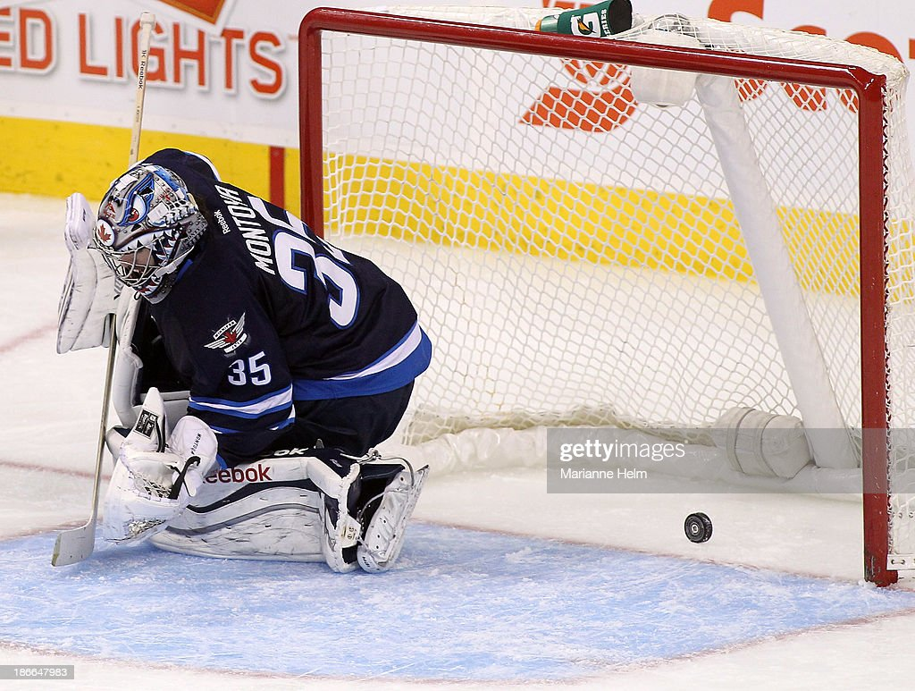 The puck bounces behind <a gi-track='captionPersonalityLinkClicked' href=/galleries/search?phrase=Al+Montoya&family=editorial&specificpeople=213916 ng-click='$event.stopPropagation()'>Al Montoya</a> #35 of the Winnipeg Jets after Ben Smith #28 of the Chicago Blackhawks (not shown) scores a goal in third period action in an NHL game at the MTS Centre on November 2, 2013 in Winnipeg, Manitoba, Canada.