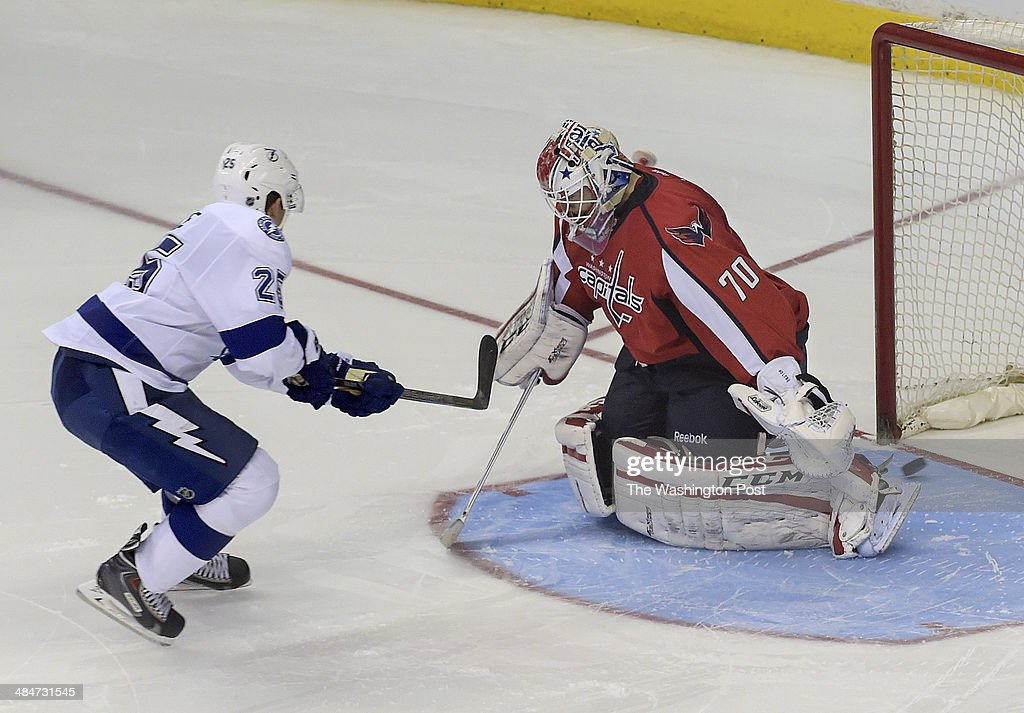 The puck bounces into the net after Tampa Bay Lightning defenseman Matt Carle (25) gets it through the legs of Washington Capitals goalie Braden Holtby (70) during a shootout to determine the winner of the game between the Washington Capitals and the Tampa Bay Lightning at the Verizon Center on Sunday, April 13, 2014. The Tampa Bay Lightning defeated the Washington Capitals 1-0 in the shoot out.