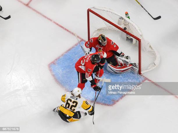 The puck bounces over the net of goaltender Craig Anderson of the Ottawa Senators while teammate Colin White defends the crease near Carl Hagelin of...