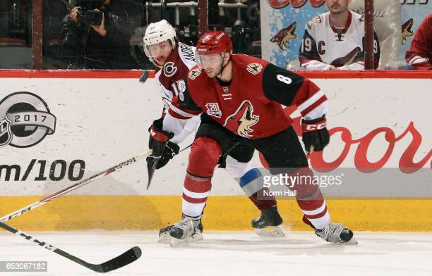 The puck bounces up in the air in front of Tobias Rieder of the Arizona Coyotes and Sven Andrighetto of the Colorado Avalanche during the first...
