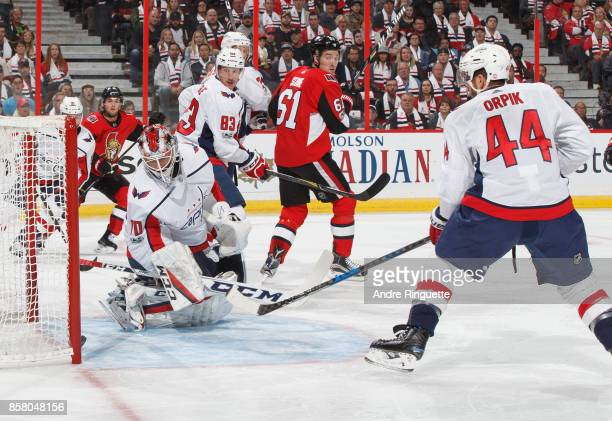 The puck crosses the goal line behind Braden Holtby of the Washington Capitals for a first period goal as teammates Jay Beagle and Brooks Orpik look...