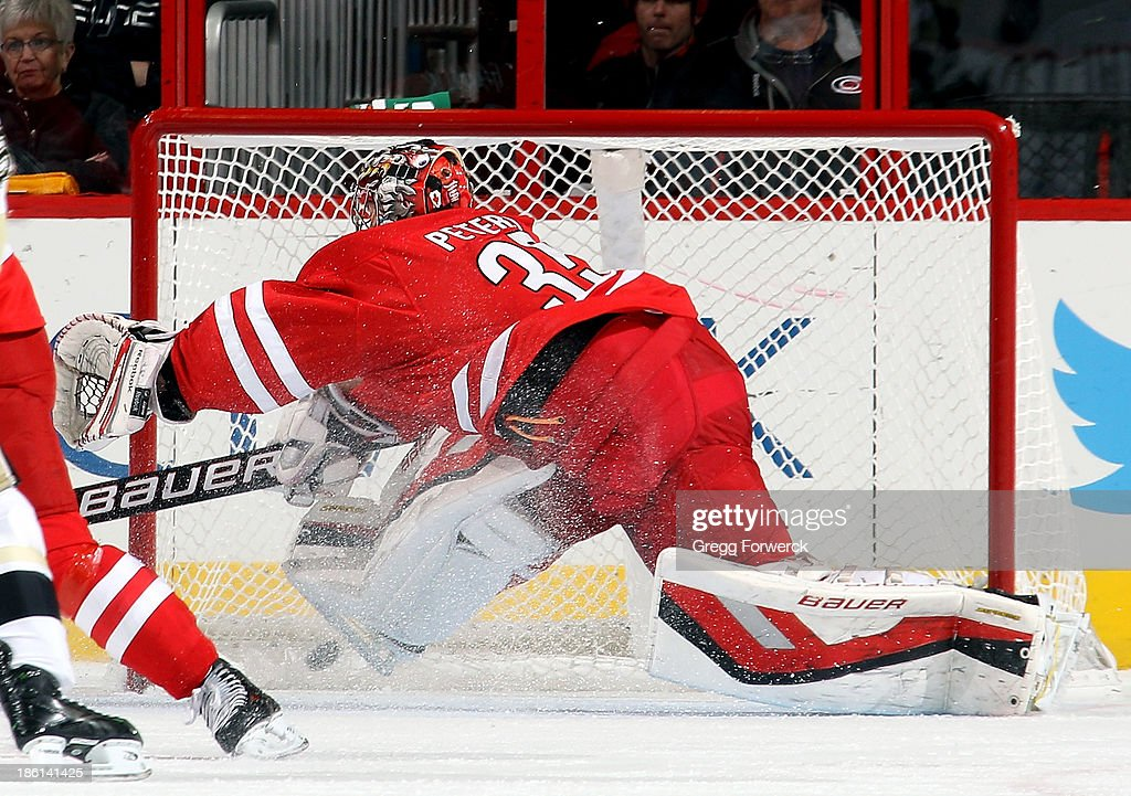 The puck finds the back of the net as Justin Peters #35 of the Carolina Hurricanes cannot block a shot from Tanner Glass of the Pittsburgh Penguins during the first period of their NHL game at PNC Arena on October 28, 2013 in Raleigh, North Carolina.