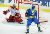 The puck flies past Danish goalie Peter Hirsch and into the net as Magnus Kahnberg of Sweden who assisted on the goal by Niklas Andersson looks on in...