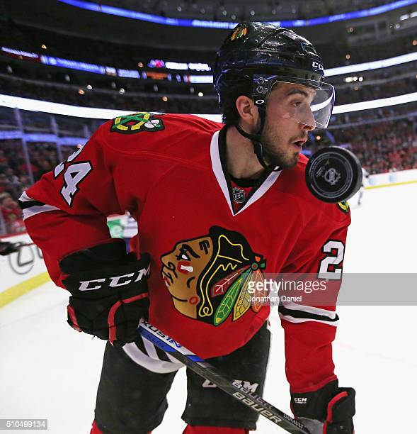 The puck flies past the face of Phillip Danault of the Chicago Blackhawks during a game against the Toronto Maple Leafs at the United Center on...