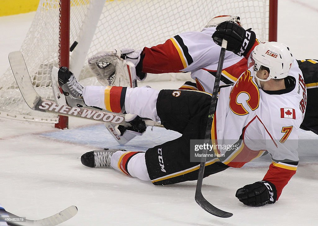 The puck gets past goaltender Reto Berra #29 and <a gi-track='captionPersonalityLinkClicked' href=/galleries/search?phrase=TJ+Brodie&family=editorial&specificpeople=7220398 ng-click='$event.stopPropagation()'>TJ Brodie</a> #7 of the Calgary Flames as Bryan Little #18 of the Winnipeg Jets (not shown) scores a goal in third period action in an NHL game at the MTS Centre on November 18, 2013 in Winnipeg, Manitoba, Canada.
