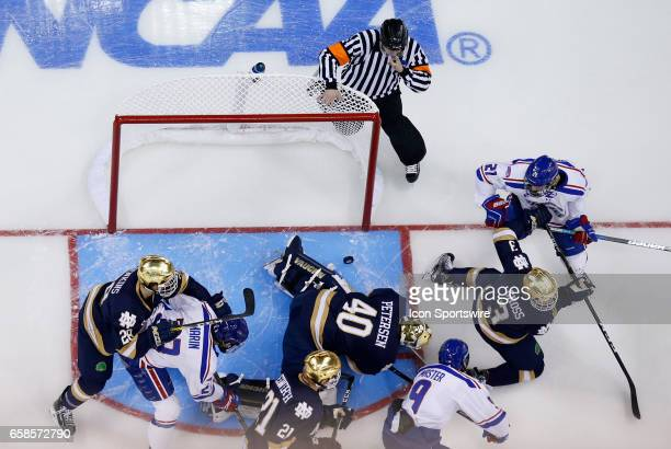 The puck gets past Notre Dame Fighting Irish goaltender Cal Petersen but not over the line as the teams battle during the NCAA Northeast Regional...