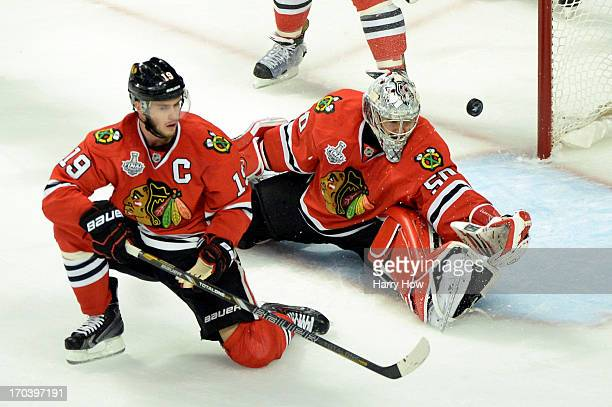 The puck goes into the net off of the stick of Milan Lucic of the Boston Bruins past Jonathan Toews and goalie Corey Crawford of the Chicago...