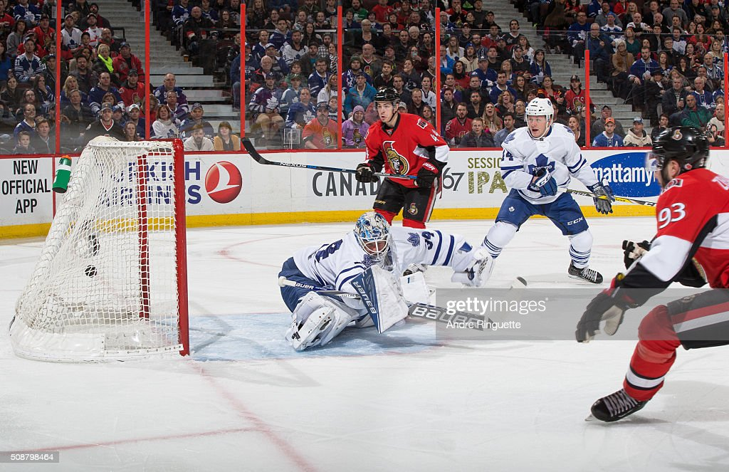 The puck hits the back of the net behind <a gi-track='captionPersonalityLinkClicked' href=/galleries/search?phrase=James+Reimer+-+Hockey+Player&family=editorial&specificpeople=7543302 ng-click='$event.stopPropagation()'>James Reimer</a> #34 of the Toronto Maple Leafs on a first period goal by <a gi-track='captionPersonalityLinkClicked' href=/galleries/search?phrase=Mika+Zibanejad&family=editorial&specificpeople=7832310 ng-click='$event.stopPropagation()'>Mika Zibanejad</a> #93 of the Ottawa Senators with <a gi-track='captionPersonalityLinkClicked' href=/galleries/search?phrase=Jean-Gabriel+Pageau&family=editorial&specificpeople=7895476 ng-click='$event.stopPropagation()'>Jean-Gabriel Pageau</a> #44 and <a gi-track='captionPersonalityLinkClicked' href=/galleries/search?phrase=Morgan+Rielly&family=editorial&specificpeople=8050727 ng-click='$event.stopPropagation()'>Morgan Rielly</a> #44 looking on at Canadian Tire Centre on February 6, 2016 in Ottawa, Ontario, Canada.