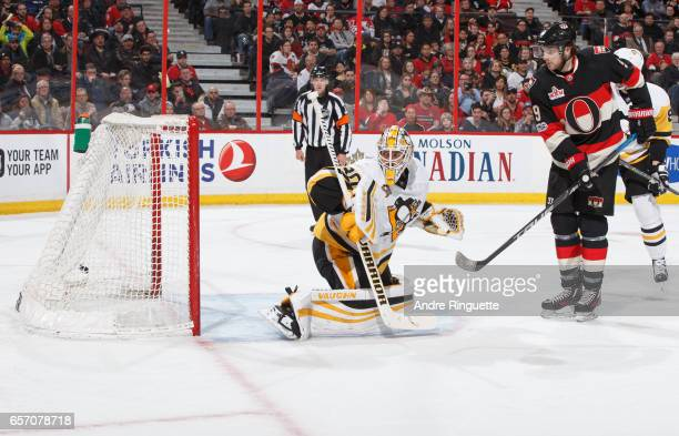 The puck hits the back of the net behind Matt Murray of the Pittsburgh Penguins for a third period goal as Bobby Ryan of the Ottawa Senators looks on...