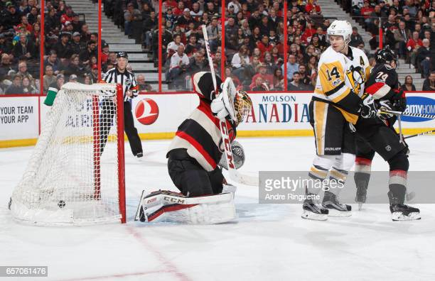 The puck hits the back of the net behind Mike Condon of the Ottawa Senators for a second period goal as Chris Kunitz of the Pittsburgh Penguins looks...