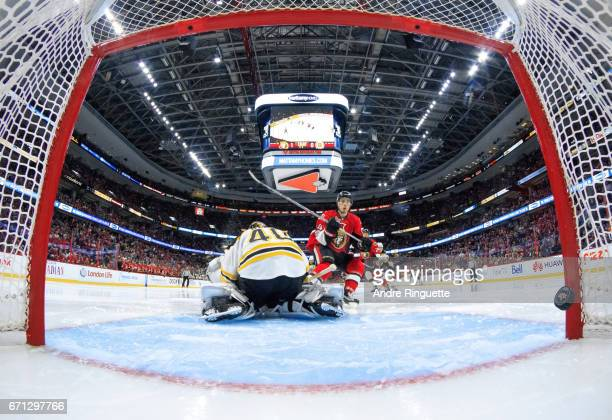 The puck hits the back of the net behind Tuukka Rask of the Boston Bruins for a second period goal by JeanGabriel Pageau of the Ottawa Senators in...