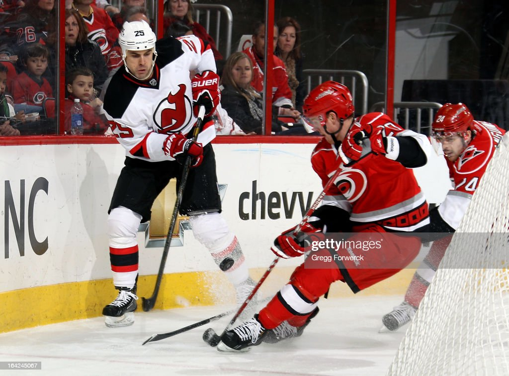 The puck is chipped between Riley Nash #20 of the Carolina Hurricanes and <a gi-track='captionPersonalityLinkClicked' href=/galleries/search?phrase=Tom+Kostopoulos&family=editorial&specificpeople=209030 ng-click='$event.stopPropagation()'>Tom Kostopoulos</a> #25 of the New Jersey Devils behind the Hurricanes net during their NHL game at PNC Arena on March 21, 2013 in Raleigh, North Carolina.
