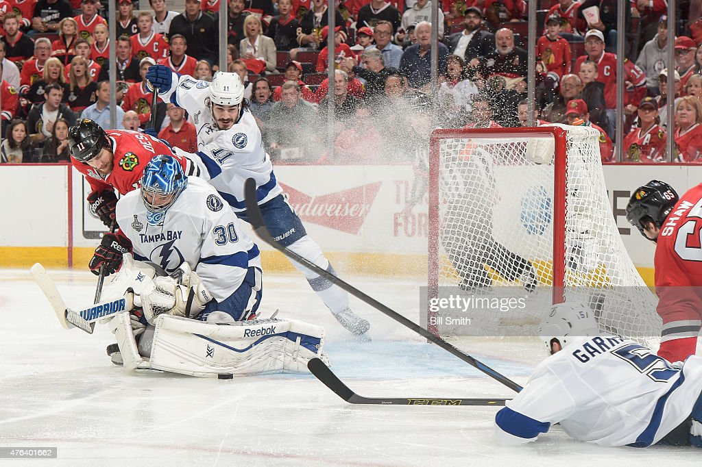 The puck is stopped by goalie Ben Bishop #30 of the Tampa Bay Lightning as Andrew Desjardins #11 of the Chicago Blackhawks and Brian Boyle #11 watch from behind during Game Three of the 2015 NHL Stanley Cup Final at the United Center on June 8, 2015 in Chicago, Illinois.
