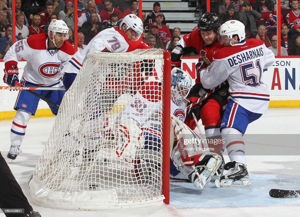 The puck sits in the net behind Peter Budaj #30 of the Montreal Canadiens for a third period goal as Zack Smith #15 of the Ottawa Senators crashes the net against Francis Bouillon #55, Andrei Markov #79 and David Desharnais #51 of the Ottawa Senators on January 30, 2013 at Scotiabank Place in Ottawa, Ontario, Canada.