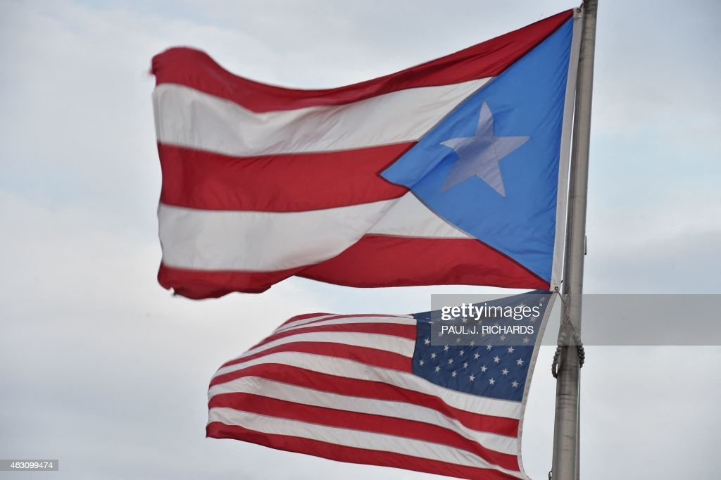 The Puerto Rican and US flags are seen in the Old Town district February 9 2015 in San Juan Puerto Rico AFP PHOTO/PAUL J RICHARDS