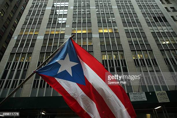 The Puerto Rican flag flies as people protest outside of Wall Street against cutbacks and austerity measures forced onto the severely indebted island...
